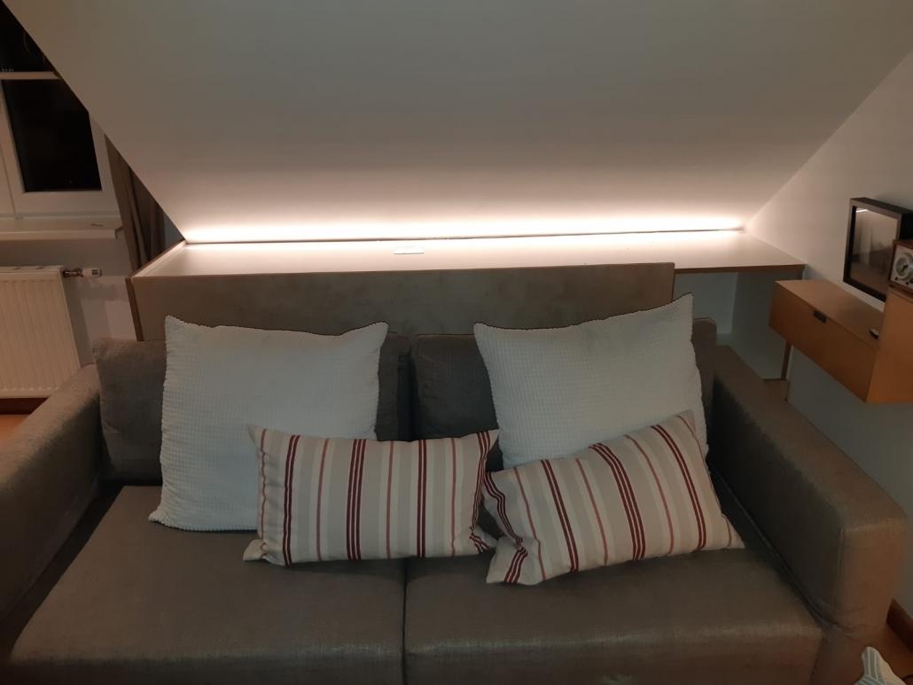 Bettzeugschrank hinter Couch mit integrierter Beleuchtung